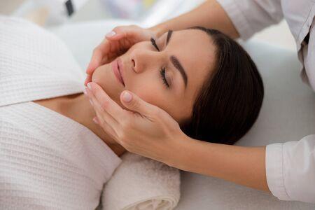 Masażystka masująca twarz pani w salonie kosmetycznym