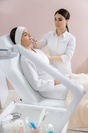 Charming young woman receiving face massage at spa salon