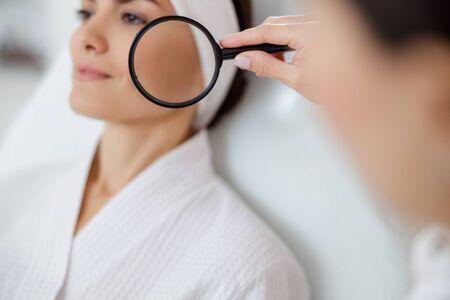 Kosmetikerin, die Lupe in der Nähe des Gesichts der lächelnden jungen Frau hält stockfoto