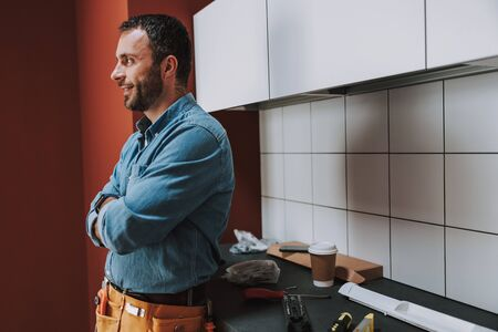 Happy young man looking away in the kitchen Stockfoto
