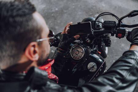 Brutal Caucasian motorcyclist enjoying new modern motorbike stock photo Stok Fotoğraf