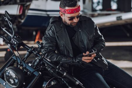 Calm adult man in black leather jacket using his smartphone stock photo