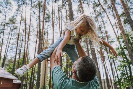 Père soulevant sa fille en l'air Banque d'images