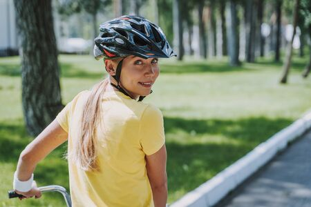 Beautiful woman in safety helmet riding bicycle outdoors Imagens