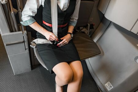 Caucasian young flight attendant seating her belt on board