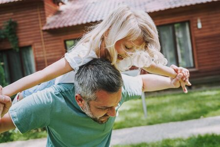 Cheerful little girl riding on father back outdoors Imagens