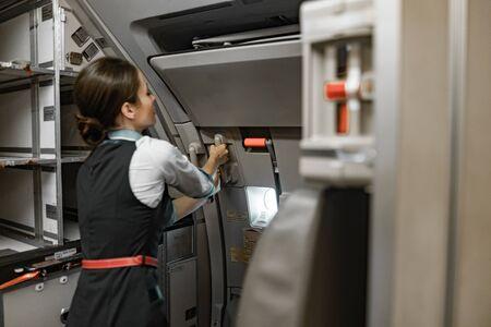 Asistente de vuelo hembra adulta está de servicio a bordo del avión