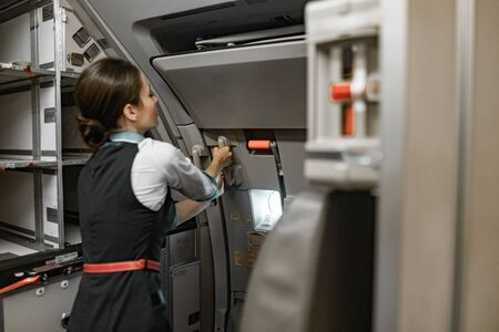 Eine erwachsene Flugbegleiterin ist an Bord des Flugzeugs im Dienst
