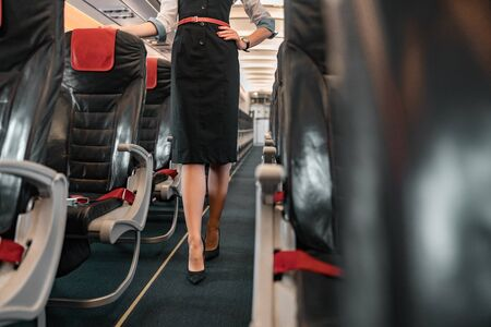 Caucasian stewardess walking in aisle of airliner stock photo. Airways concept