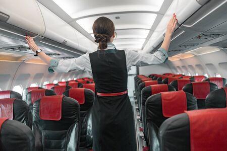 Auxiliar de vuelo femenino haciendo su trabajo en la fotografía de stock de avión. Concepto de vías aéreas