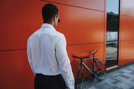 Focus on back of man in office clothes. He is going to his bike parked near workplace for cycling home. Copy space in right side