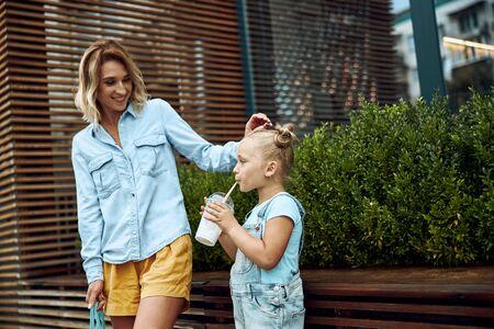 Mother watching her daughter drinking milkshake stock photo