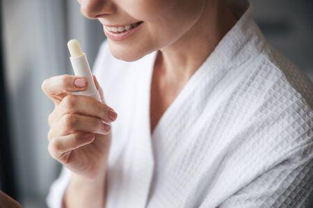Fröhliche junge Frau, die ihren neuen Lippenstift vorführt