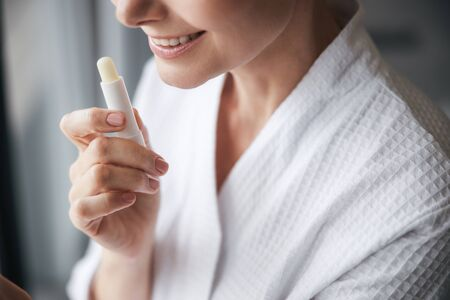 Cheerful young woman demonstrating her new lipstick