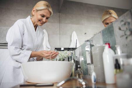 Charmante blonde vrouw die haar handen wast voor spa