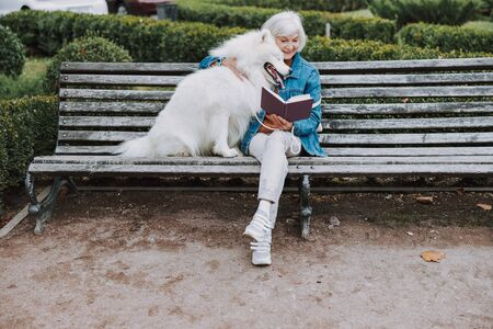 Happy elderly woman reading book to her cute dog in park