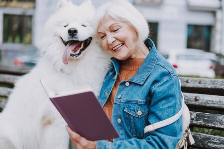 Elderly woman reading book to her cute dog in park