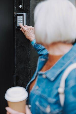 Elderly lady is ringing the buzzer at door