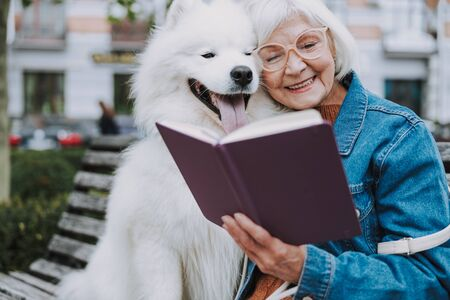 Happy adult Caucasian woman in glasses reading book