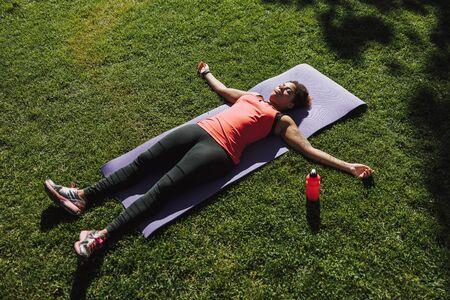 Charmante junge Frau liegt auf der Yogamatte auf der Straße Standard-Bild