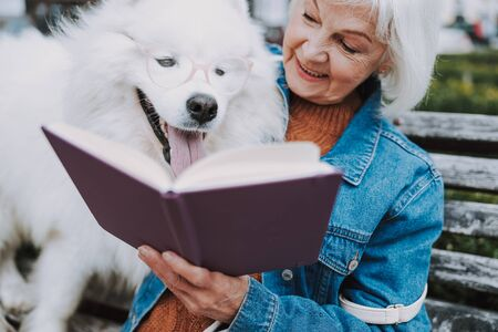 Happy elderly woman showing book to her cute dog
