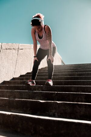 Sporty young woman standing bent over on stairs outdoors