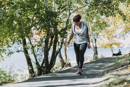 Afro American young woman in sportswear strolling through the park stock photo