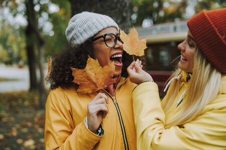 Happy and smiling women holding leaves in hands stock photo