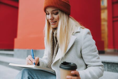 Happy female student with coffee to go writing in copybook
