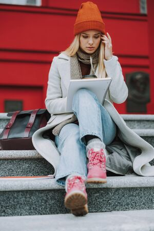 Young female student girl looking at copybook