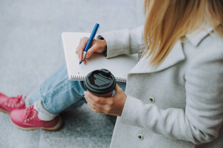 Female student with coffee to go writing in copybook Stockfoto
