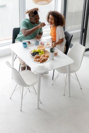 Joyful man feeding his girlfriend in cafe
