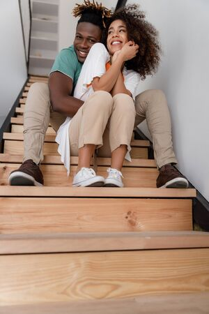 Happy young couple sitting on stairs at home
