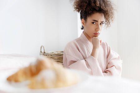 Señora afroamericana molesta mirando croissants