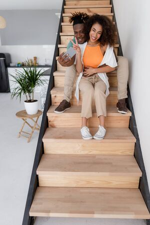 Beautiful young couple sitting on stairs and making selfie