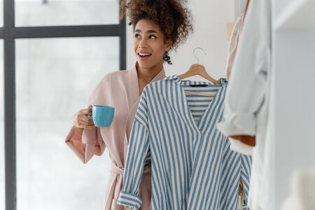 Smiling young woman holding shirt and cup of coffee