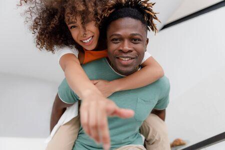 Joyful Afro American man giving his girlfriend piggyback