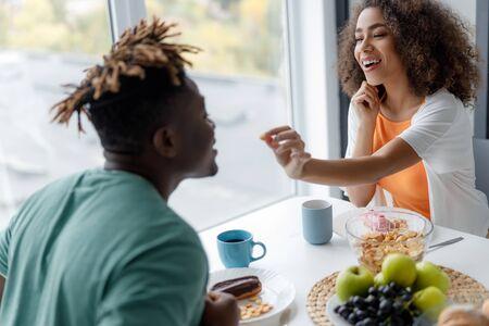 Cheerful young woman feeding her boyfriend in cafe