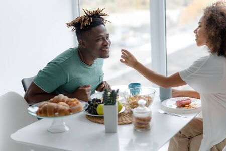 Cheerful young lady feeding her boyfriend in cafe