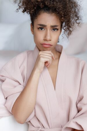 Upset Afro American lady in bathrobe pouting lips