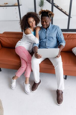 Beautiful young couple using laptop at home