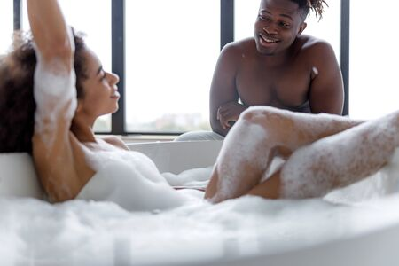 Charming young lady lying in bathtub and looking at her boyfriend Stock fotó