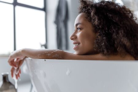 Charming Afro American woman relaxing in bath 版權商用圖片