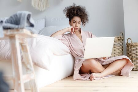 Annoyed young woman with laptop sitting on the floor