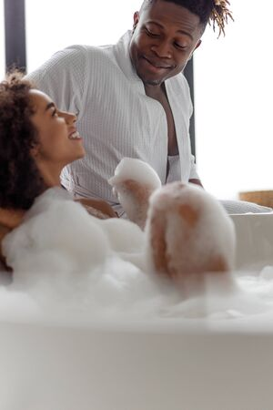 Cute young lady looking at her boyfriend while taking bath Stock fotó