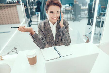 Happy young lady using smartphobe in office stock photo Reklamní fotografie
