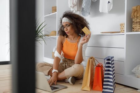 Annoyed lady doing online shopping with notebook