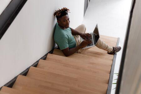 Handsome Afro American man using modern laptop