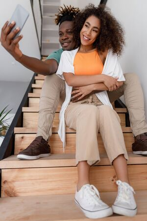 Joyful man hugging lady and making selfie Stock fotó
