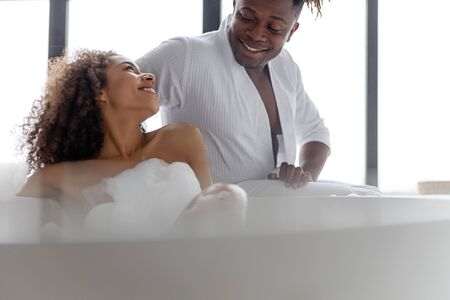 Smiling lady looking at her boyfriend while taking bath